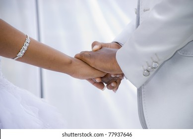 African Couple getting married under a white outdoor tent. Image of their hands against the white tent interior.