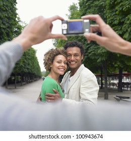 African couple having photograph taken in park