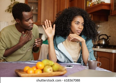 African couple having quarrel at home. Unhappy husband apologizing for an affair to his offended angry wife who is not accepting all his excuses. Black man begging his girlfriend for forgiveness