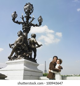 African couple hugging next to statue in Paris
