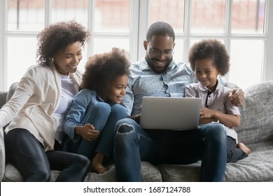 African couple and kids look at pc screen engaged at search of best offer travel full family trip, booking hotels use websites services buy on-line, make videocall, surfing web, watch cartoons concept