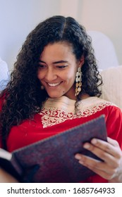African culture indoors at the house. Portrait of young female with muslim lifestyle. Beautiful ethnic woman writing on a notebook at home. Moroccan female with traditional clothes with copyspace.