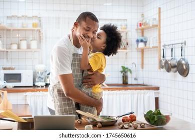 Afrikanischer Cute kleiner Junge in gelb, der Papa beim Kochen zuhause küsst. Glücklich lächelnd afroamerikanischer Vater während Umarmung und tragen seinen Sohn in der Küche. Freuen Sie sich auf die schwarze Familie, lieben Sie Emotionen.