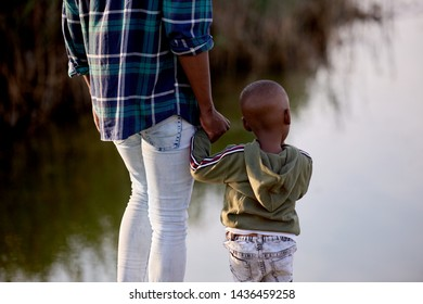 African dad father holding his kid son hand looking out at the lake, aspirational dreaming for the future