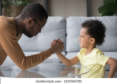 African dad and kid son with funny angry faces arm wrestling having fight showing family power, black baby sitter or father in law and stubborn child boy toddler holding hands play competing at home