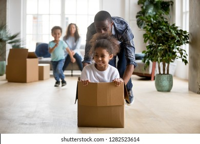 African dad playing with mixed race daughter riding in box on moving day concept, little kids enjoy game with father in living room, happy black family and children having fun in new home, relocation