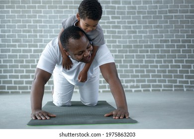 African dad and son exercise on floor at home, man pushup from the floor with the boy on his back, father's day