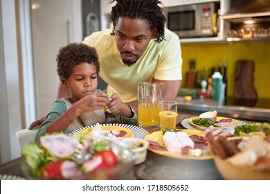 african dad and son together in the kitchen analyzing food for breakfast. healthy, food, family concept
