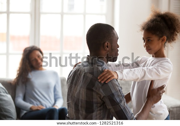 African dad talking to daughter supporting or explaining little mixed race girl during friendly conversation at home, black father speaking to child having good trustful relationships with kid