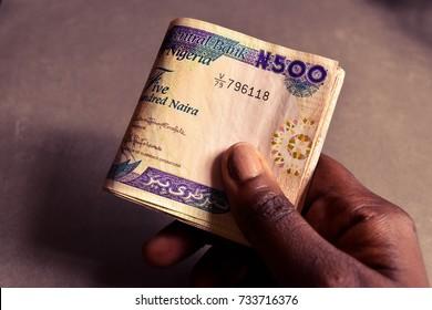 African Dark skin hand holding folded five hundred naira notes