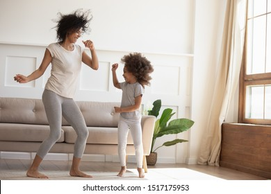 African daughter and mother dancing in modern cozy sunny living room, babysitter and little kid enjoy summer day at home, family celebrating vacation, leisure, funny mood, happy active people concept