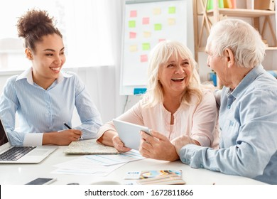 African descent woman travel agent at office looking at senior couple holding digital tablet browsing travel application smiling joyful