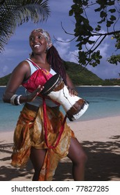 African drummer plays a small djembe drum on the beach by the ocean.