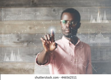 African employee, pushing a glowing button at futuristic technology touchscreen display of a main computer to zoom a subject, against wooden interior of his office. Double exposure. Visual effects