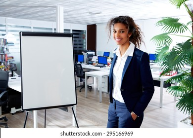 african ethnic executive woman with presentation board in office standing happy