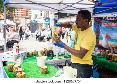African ethnic preparing pina colada in pineapple on street - Food Street Market Reading, United Kingdom - June 2nd, 2018
