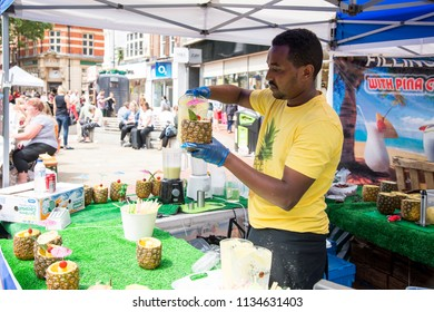 African ethnic preparing pina colada in pineapple on street - Food Street Market Reading, United Kingdom - June 2, 2018