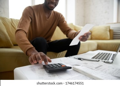 African ethnicity man sitting on couch calculates digits using calculator planning family budget check bills cheques, heap of bill financial papers documents and notebook on coffee table close up view