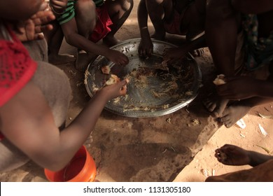 african every day life  detail - traditional meal:  photography of kids eating traditional ramadan pasta meal, outdoors with a natural light, in the Gambia, Africa, on a sunny day