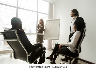 African executive team listening to business coach giving presentation at meeting, female leader presenting new sales strategy or making offer to partners explaining marketing project on flipchart
