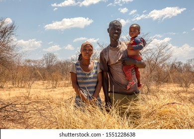 African family with a child in a village in  Botswana standing in front of  the bush in Kalahari , Botswana
