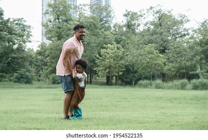 African family dad and little son playing in green park. Active boy is holding daddy's hand and standing on his father's feet and will walk along the way. They enjoy and spend time together on weekend