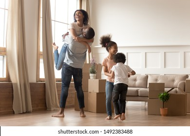African family enjoy relocation day at new cozy home big carton boxes as symbol of housing improvement, husband lifting up holding wife on hands, little kids dancing feels happy, loan mortgage concept