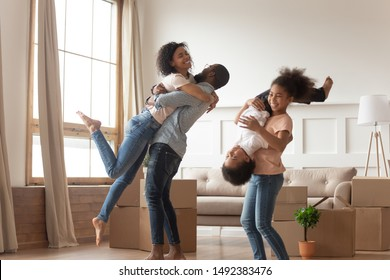 African family fooling around in living room celebrating moving day at new home big carton boxes as symbol of relocation, husband lifting up beloved wife, older sisters hold turned upside down brother