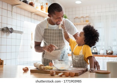 African family have fun cooking baking cake or cookie in the kitchen together, Happy smiling Black son enjoy playing and touching his father nose with finger and flour while doing bakery at home.