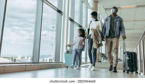 African family with luggage walking by window at airport terminal and watching airplanes through glass window. Family walking through airport passageway.