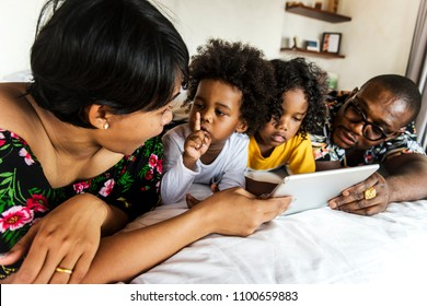 African family on bed using a tablet