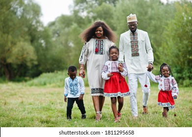 African family in traditional clothes at park.