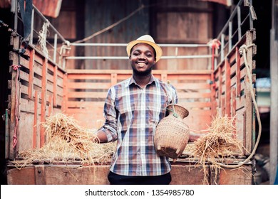 African farmer smiling and standing with small tractor on the countryside