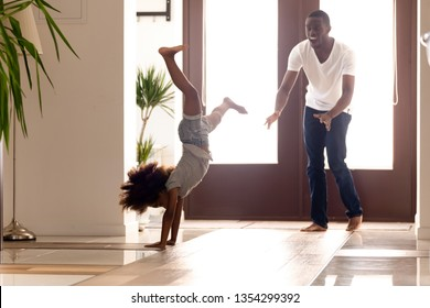 African father and daughter having fun at home hallway sportive active little kid show to daddy how she makes do handstand position dad feels amazed surprised. Funny leisure activities indoors concept