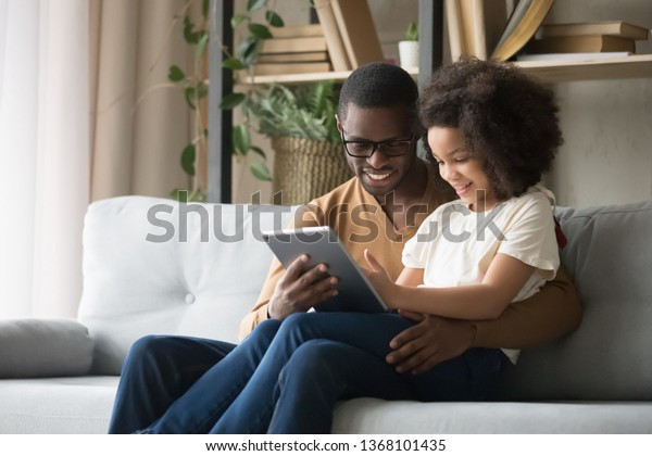 African father holds on lap daughter sitting resting on sofa in living room using digital tablet holding mobile computer watch cartoons educational online program, buying shopping via internet concept
