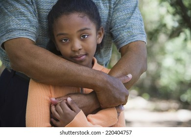 African father hugging young daughter outdoors