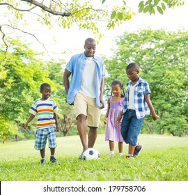 African Father Playing Ball with Children in Park