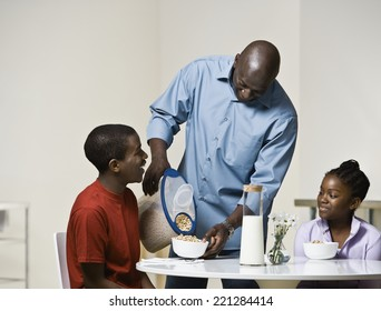 African father pouring cereal for son