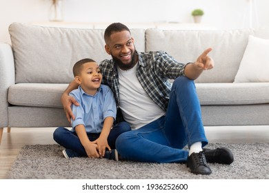 African Father And Son Hugging Sitting On Floor At Home