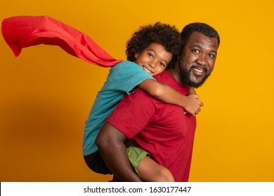 African Father and Son playing Superhero at the day time. People having fun yellow background. Concept of friendly family.