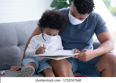 African father and son with protective masks drawn picture together on couch, protect infection from coronavirus covid-19 on table, the new normal social distancing concept