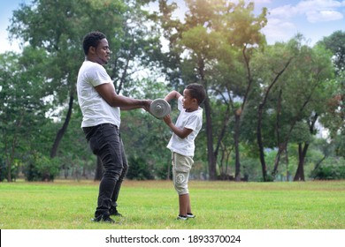 African father teaching his son exercising with dumbbells in green park, spend time together at outdoor park, Father's day