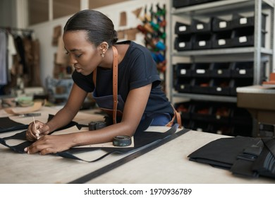 African female artisan using a pattern on leather in her shop