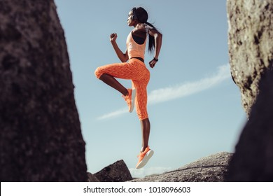 African female athlete jumping and stretching over rocks outdoors. Healthy and tough woman exercising.