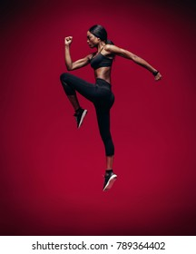African female athlete jumping and stretching over red background. Healthy and tough woman exercising.