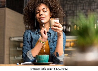 african female demonstrating thoughtfulness while eating dessert at table. She listening music while locating in cafe
