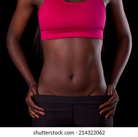 African female fit torso with exposed belly area on black background. Workout and healthy lifestyle result concept