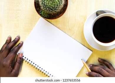 African Female hand writing on notebook surrounded with office accessories. Top view of work desk. Coffee, pencil, cactus succulent plant