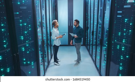African female head administrator walking with server technician showing digital room at database. Couple of diverse specialists cooperating in data center.