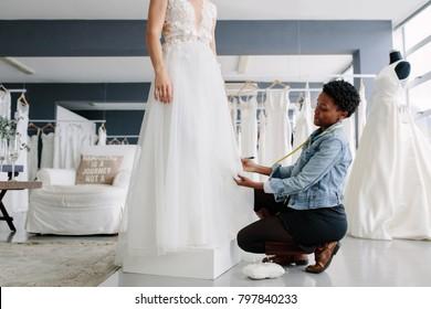 African female making adjustment to wedding gown in fashion designer studio. Bride standing in her wedding gown with female dress designer making final adjustments on dress.